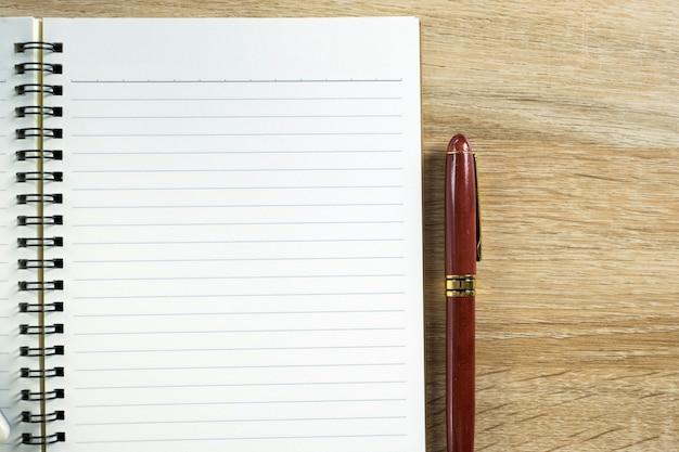 Estilográfica o bolígrafo de tinta con papel de cuaderno sobre madera.