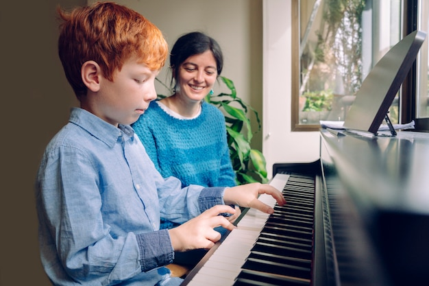 Estilos de vida familiares con niños. actividades educativas en el hogar. chico joven de pelo rojo tocando el piano. niño pequeño que ensaya lecciones de música en un teclado en casa. estudia y aprende el concepto de carrera musical.