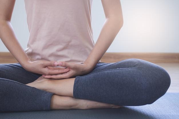Estilos de vida de yoga y meditación. vista cercana de joven bella mujer practicando yoga namaste pose en la sala de estar en casa.