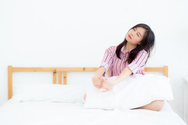 El estiramiento asiático hermoso de la mujer y se relaja en cama