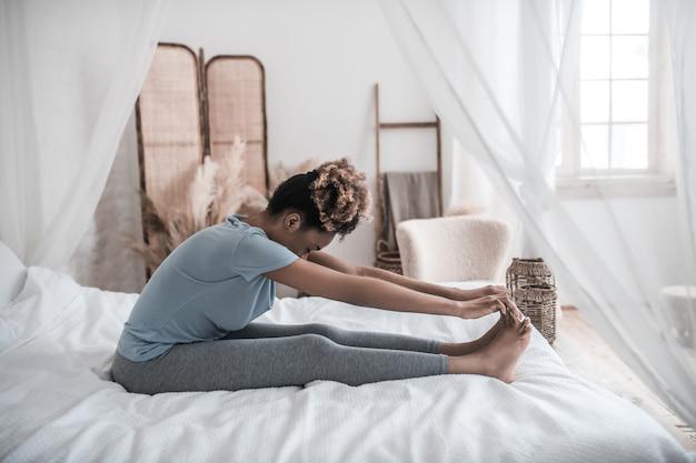 Estiramiento matutino. mujer joven de piel oscura sentada en la cama con la cabeza baja a los pies sosteniendo sus dedos de los pies con las manos