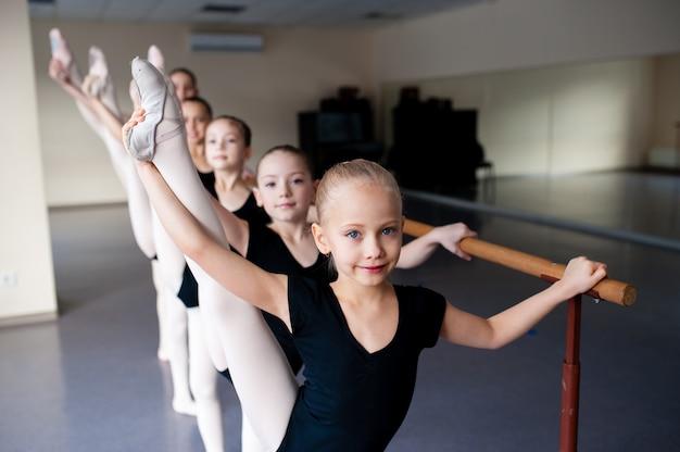 Estiramiento, niños en clase de danza de ballet.