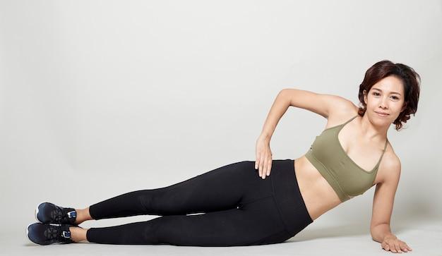 Estiramiento postura de entrenamiento por una mujer asiática sobre fondo gris estudio