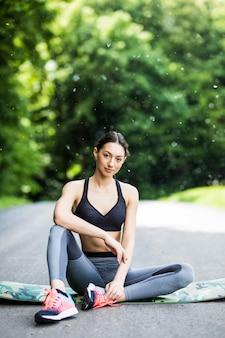 Estirar a la mujer en ejercicio al aire libre sonriendo feliz haciendo yoga se extiende después de correr.