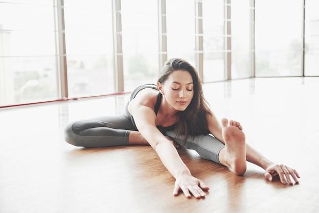Estirar a una mujer gimnasta hace una división, una cuerda en un gimnasio.