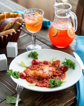 Estofado de carne de pollo en salsa de tomate con hierbas y jugo de naranja.
