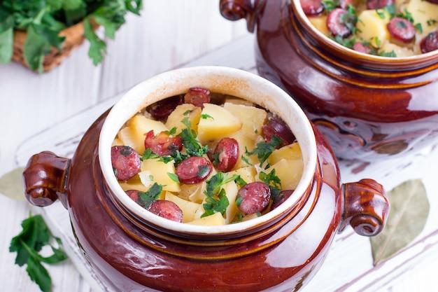 Estofado de papa caliente con tocino y salchichas servido en un cuenco de cerámica