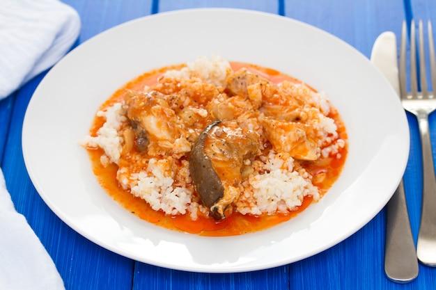 Estofado de pescado con arroz en plato blanco sobre superficie de madera