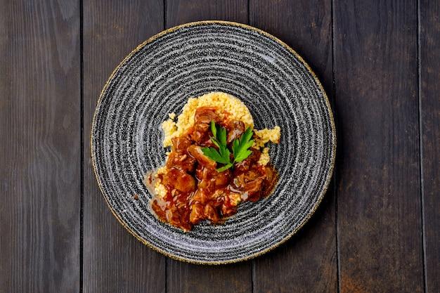Estofado de ternera con gachas de mijo y salsa cremosa en la mesa de madera oscura