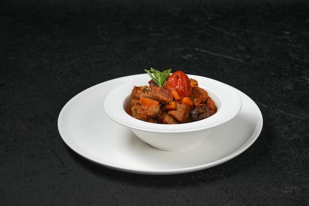 Estofado de ternera con tomate en un plato