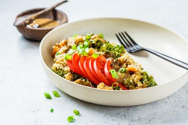 Estofado vegano con garbanzos, camote y tomate fresco en un plato blanco.