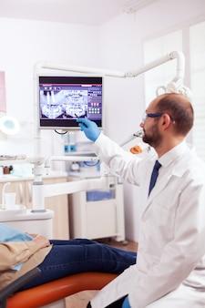 Estomatólogo explicando el tratamiento dental a la mujer mayor durante el examen mirando rayos x. tomador de atención médica de los dientes apuntando a la radiografía del paciente en la pantalla sentado en una silla.