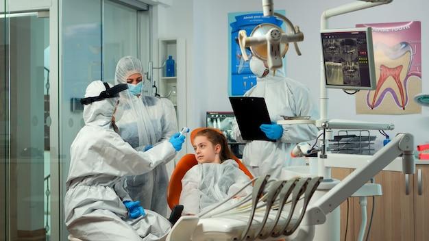 Estomatólogo con protector facial que mide la temperatura de la niña antes del examen dental durante la pandemia mundial. concepto de nueva visita al dentista normal en el brote de coronavirus con traje protector.