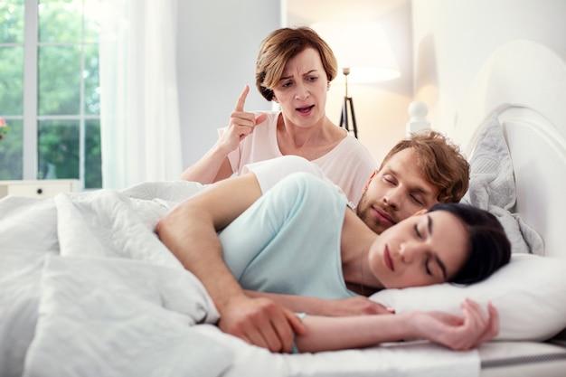 Estoy aquí. agradable mujer de edad sentada en la cama mientras crea problemas para la pareja