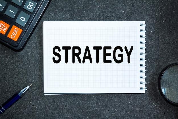 Estrategia de texto. escritorio de oficina, calculadora, bloc de notas con documentos. concepto de negocio