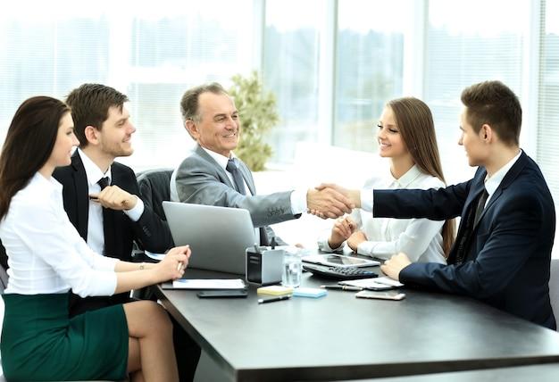Estrechar la mano durante una reunión de negocios socios comerciales en la oficina
