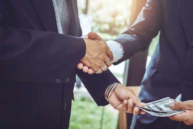 Estrecharme la mano trabajando juntos dos hombre de negocios.