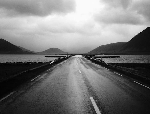 Un estrecho puente de carretera con hermoso cielo y un lago