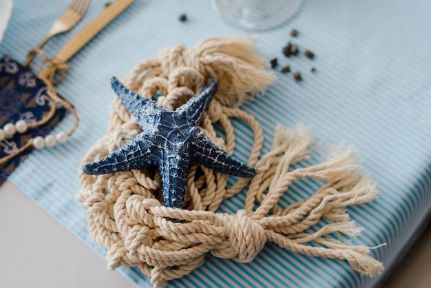 Estrella de mar y cuerda en el viejo fondo azul agrietado. concepto de vacaciones