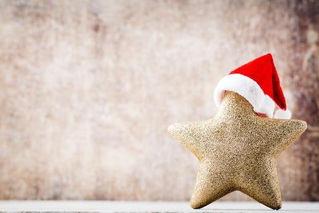 Estrella de navidad con gorro de papá noel. fondo de añadas.