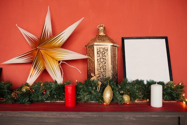 Estrella de navidad, linterna y guirnalda de árbol de navidad, decoración navideña en pared roja