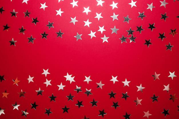 La estrella de plata asperja en backgound rojo. confeti festivo de vacaciones. concepto de celebración