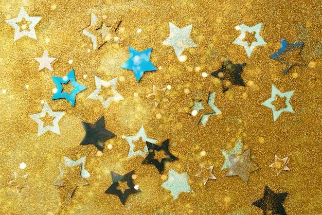Estrellas azules, amarillas sobre fondo de oro con bokeh.