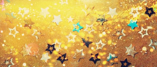 Estrellas brillantes sobre fondo de oro con bokeh