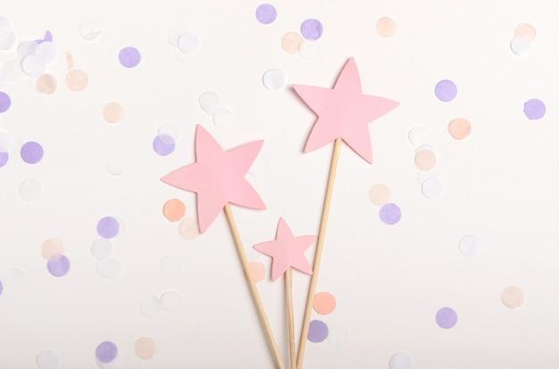Estrellas de color rosa en un palo relleno sobre fondo blanco con confeti