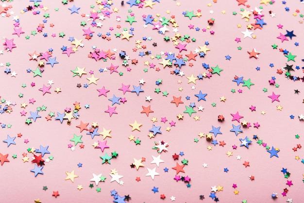 Estrellas de confeti de colores sobre fondo rosa
