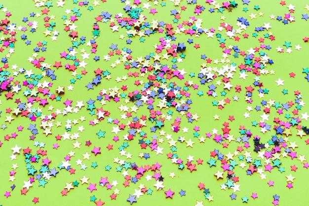 Estrellas de confeti de colores sobre fondo verde