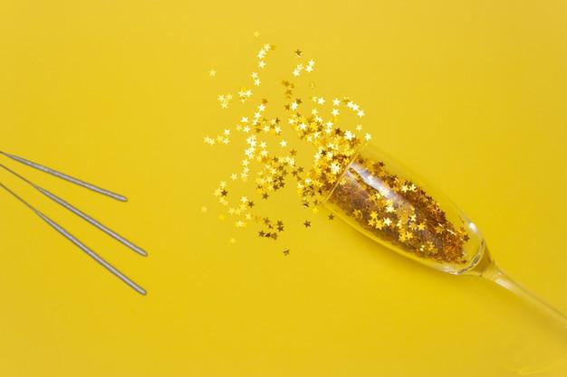 Estrellas de confeti se derraman de una copa de champán y un palo de bengala sobre un fondo amarillo