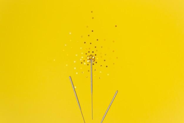 Estrellas de confeti y palos de bengala sobre un fondo amarillo