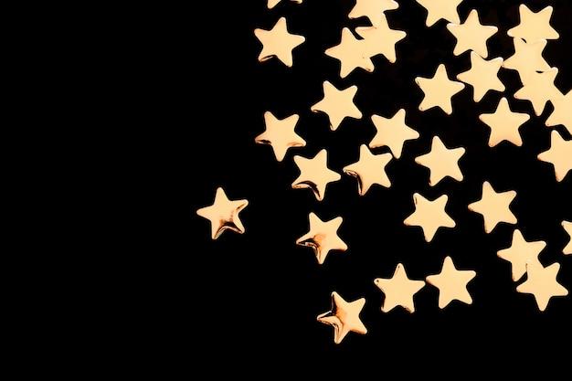 Estrellas decorativas doradas sobre fondo negro
