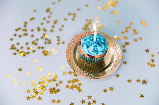 Estrellas esparcidas alrededor de la vela iluminada sobre la magdalena en un plato dorado