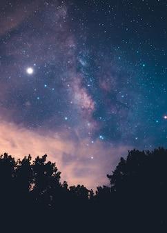 Estrellas y galaxias vía láctea en el cielo nocturno púrpura y azul