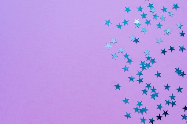 Estrellas holográficas sobre fondo morado de moda. telón de fondo festivo vista superior. copia espacio