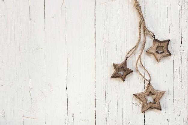 Estrellas de madera para árbol de navidad sobre fondo blanco de madera