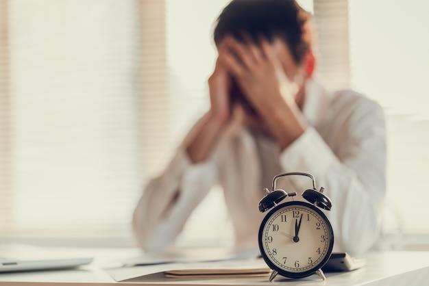 El estrés del hombre de negocios y la preocupación por la hora tardía para terminar el proyecto de trabajo