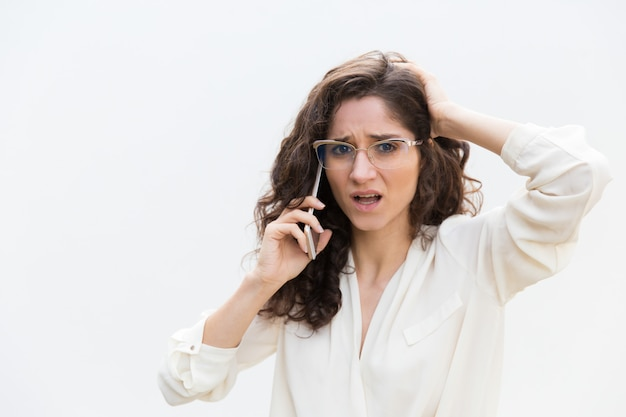 Estresada mujer perpleja con gafas hablando por teléfono móvil
