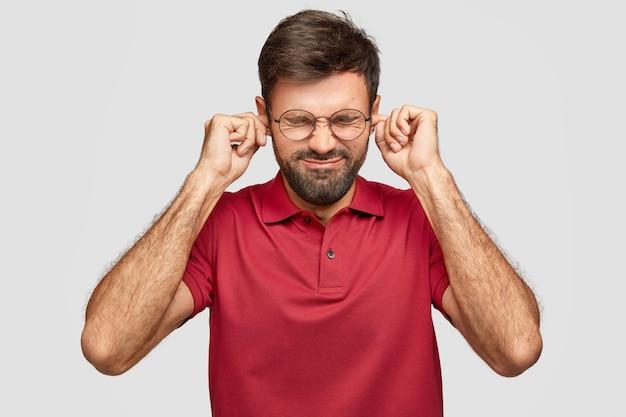 Estresante hombre caucásico barbudo tapona los oídos con los dedos, mantiene los ojos cerrados