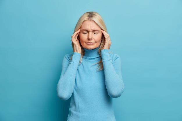 Estresante mujer rubia arrugada sufre un terrible dolor de cabeza toca las sienes se siente desagradable cierra los ojos para revelar el dolor