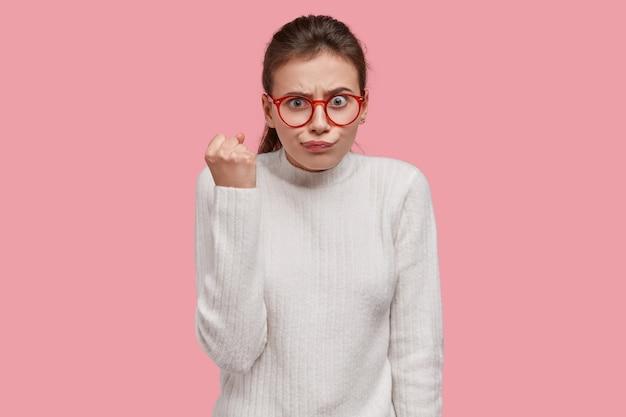Estricta dama europea con apariencia agradable, muestra el puño, usa anteojos ópticos y suéter blanco, demuestra su disgusto
