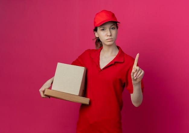 Estricta joven bonita repartidora con uniforme rojo y gorra sosteniendo el paquete de pizza y la caja de cartón levantando el dedo gesticulando no aislado sobre fondo carmesí con espacio de copia