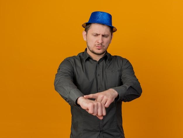Estricto chico de fiesta joven con sombrero azul shoing gesto de reloj de pulsera aislado en naranja
