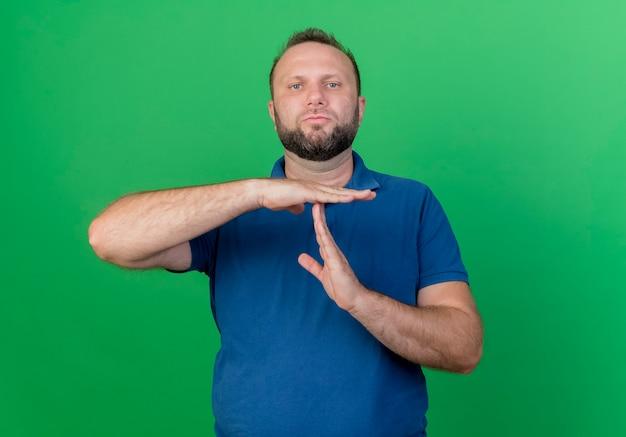 Estricto hombre eslavo adulto haciendo gesto de tiempo de espera aislado en la pared verde con espacio de copia