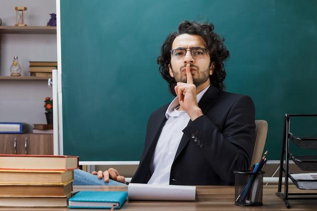 Estricto mostrando gesto de silencio profesor con gafas sentado a la mesa con herramientas escolares en el aula