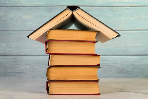 Estructura de la casa hecha con libros antiguos contra pared de madera.