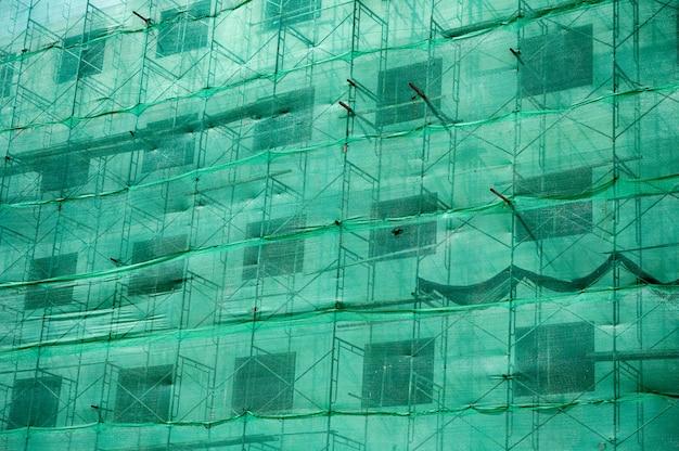 Estructura del edificio con sombra de red verde y andamios