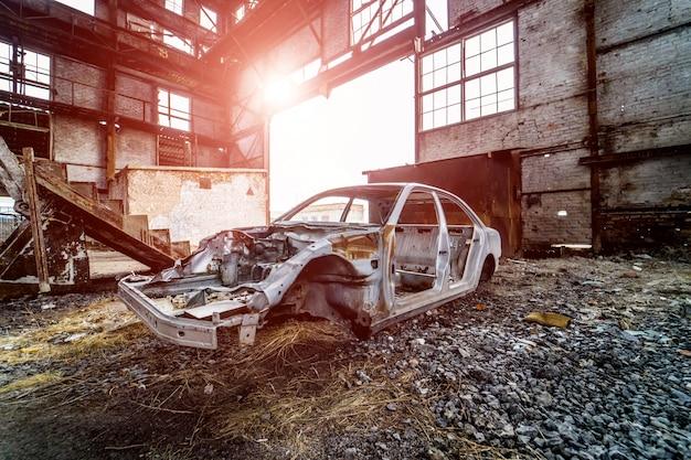 Estructura metálica de un coche oxidado en un gran edificio abandonado viejo dentro con fugas de luz.